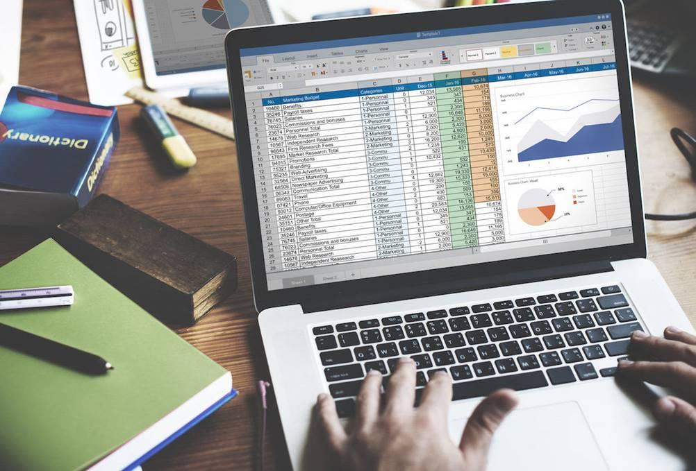 Homem trabalhando no computador com dados e gráficos de Fluxo de Caixa