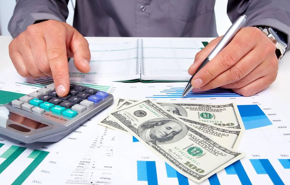 Homem trabalhando com calculadora e planilhas, equipamentos fundamentais na Gestão Financeira