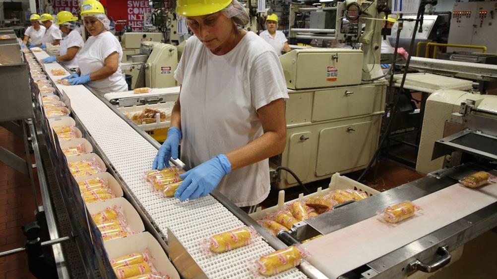 Mulher trabalhando em uma linha de produção, a qual se baseia em um Layout de produção